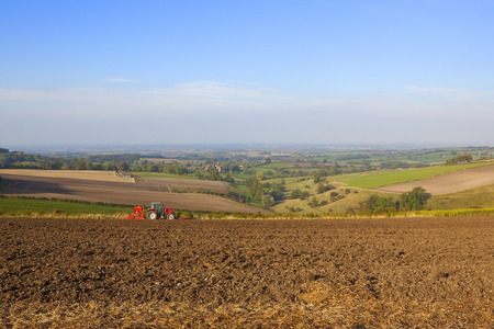 seed drill: a red tractor with a seed drill on a hillside with a colorful view of the vale of york england under a blue sky in autumn