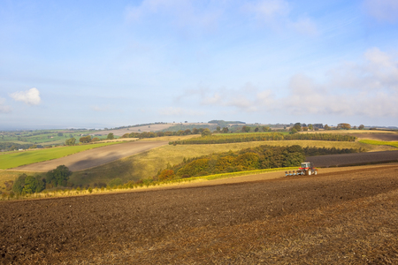 vale: a red tractor plowing a field in the yorkshire wolds england on a sunny october day in autumn with a view of the vale of york