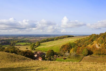 vale: a large farm estate in the yorkshire wolds england with a view of the vale of york and a colorful wooded valley in october under a blue cloudy sky Stock Photo