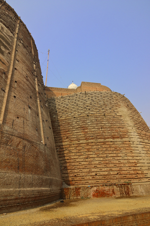 gurdwara: entrance to bathinda fort in punjab with rounded walls and a gurdwara at the top under a clear blue sky Stock Photo