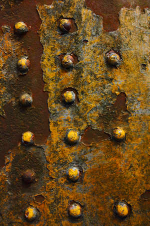 rivets: a yellow painted weathered metal surface with rivets