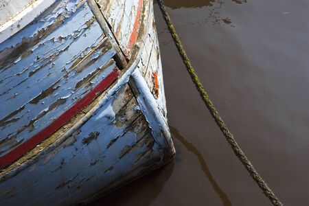bow of boat: bow of an old wooden clinker built fishing boat with flaking paint and mooring rope Stock Photo