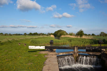 canal lock: water pouring through canal lock gates beside a canal towpath with benches and picnic area in an agricultural landscape