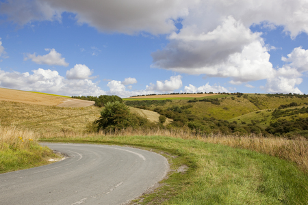 hedgerows: a valley road with scenic hills and hedgerows under a blue cloudy sky in the yorkshire wolds in summer Stock Photo