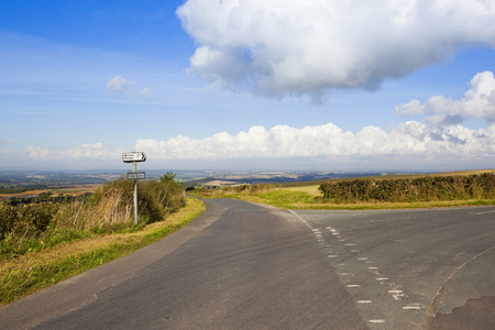 sign post: a hilltop road in the yorkshire wolds with a sign post and views of patchwork fields under a blue sky with fluffy white clouds in autumn Stock Photo