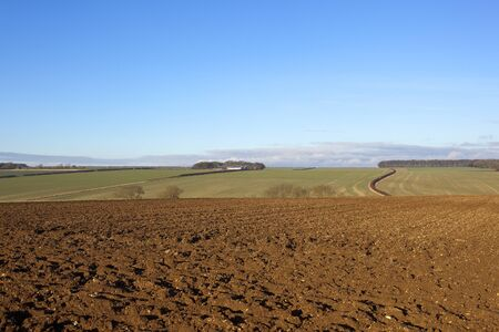 an english landscape with a hillside plowed field and scenic views in the yorkshire wolds under a blue sky in winter Stock Photo