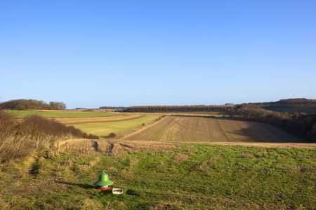 an agricultural shooting and hunting yorkshire wolds landscape with woods and hedgerows straw stubble and a pheasant feeder under a clear blue sky in winter Stock Photo