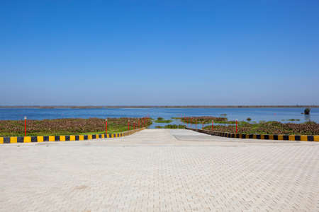 a white stone ramp with barriers going into the water at harike wetland nature reserve in punjab for the tourist amphibious bus
