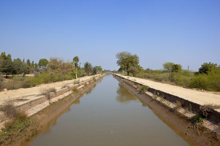 a straight rajasthan canal with tree lined sandy footpaths in india under a clear blue sky in springtime Stock Photo