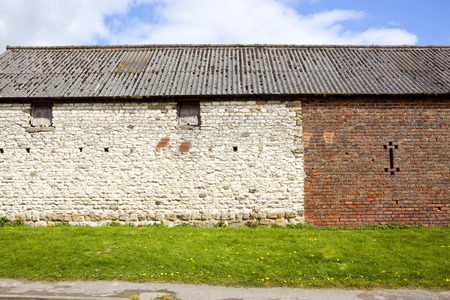 outbuilding: an old rustic barn made from white stone and orange brick with windows and wooden shutters on a grassy bank