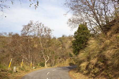 a bend in the morni hills mountain road with marker posts going through sandy hillsides and acacia forest under a blue cloudy sky near chandigarh india Stock Photo