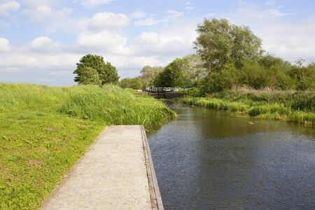 a yorkshire canal and lock with towpath woods and wildflowers and a jetty under a blue cloudy sky in summer Stock Photo