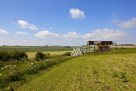 an old farm on a hill with scenic backdrop in the yorkshire wolds under a blue sky in summer