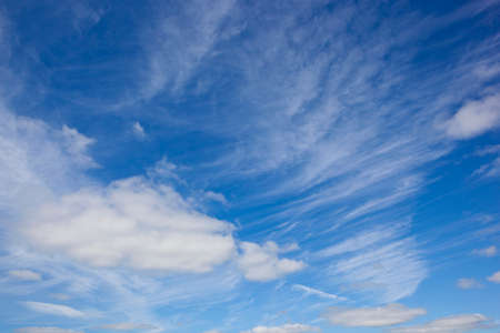 a blue sky background with wispy white clouds in summer