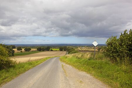 a small scenic country road with a passing place going towards a village in the yorkshire wolds under a summer stormy sky
