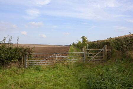 a metal farm gate and fence on a country bridleway with cultivated field under a blue cloudy autumn sky in the yorkshire wolds