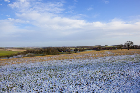 a small village in the scenic yorkshire wolds with a light covering of snow with woodland and hills under a blue cloudy sky