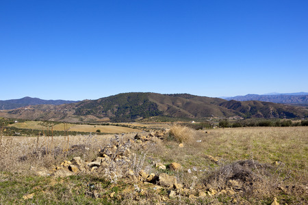 a rocky arid landscape with wooded mountains olive groves and sandy cultivated fields under a blue sky in andalusia spain Reklamní fotografie