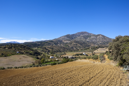 spanish mountain farmland with hillside cultivated fields olive groves and buildings under a blue sky in andalusia