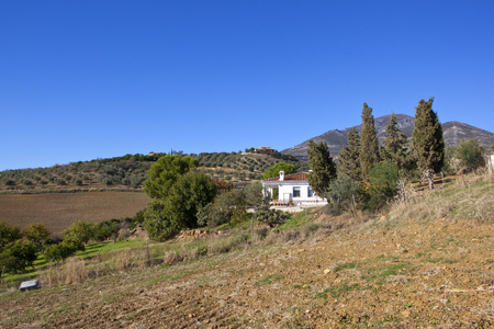 a white farming villa on a hillside with olive groves and cultivated soil near mountain scenery under a blue sky in andalusia spain