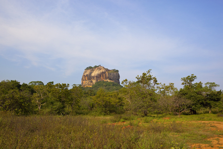 historic sigiriya rock in sri lanka with woodland and scrub on red sandy soil under a blue cloudy sky