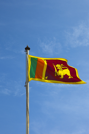 beautiful colorful sri lankan flag with flag pole against a blue sky at mount lavinia in colombo