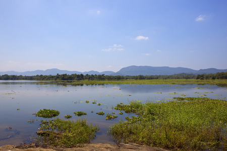 sri lankan landscape and lake at wasgamuwa national park with woodland and mountains under a blue sky