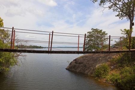 an old footbridge over the outlet from sorabora lake in a scenic sri lanka landscape Reklamní fotografie