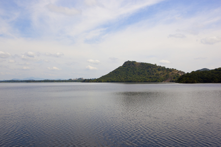 forested hills and distant mountains of a sri lankan landscape viewed across the rippled water of sorabora lake