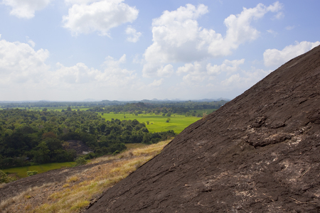 sri lankan volcanic rock formation in wasgamuwa national park with scenic landscape and hills under a blue sky with fluffy white clouds Reklamní fotografie