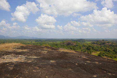 volcanic rock overlooking a sri lankan scenic vista with woodland and mountains under a blue sky with fluffy white clouds