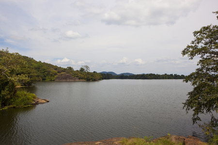 sorabora lake in sri lanka with wooded hills and lakeside scenery under a blue cloudy sky Reklamní fotografie