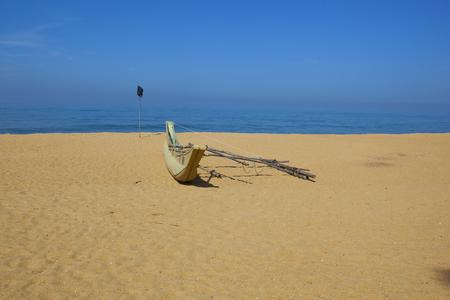 a sri lankan fishing boat on a sandy beach resort at mount lavinia colombo with blue sea and sky Reklamní fotografie