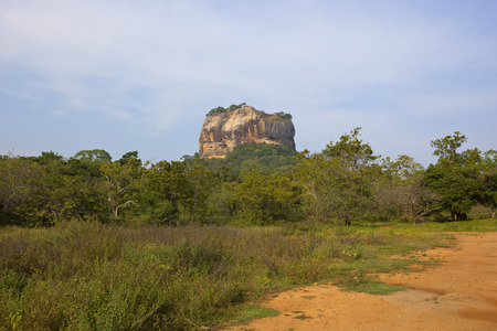 Sigiriya rock formation in rural sri lanka with tropical forest and sandy track under a blue sky