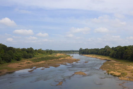 a sri lankan scenic river bed with sandy banks and tropical forest from a bridge under a blue cloudy sky Reklamní fotografie
