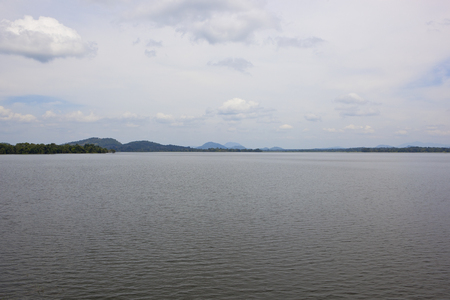 scenic sri lankan sorabora lake with wooded hills and rippled water under a blue cloudy sky