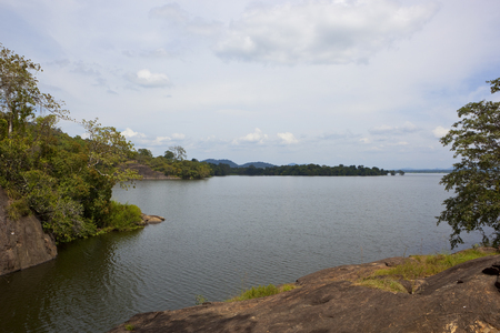 picturesque sri lankan sorabora lake with rocky banks and wooded hills overlooking rippled water under a blue cloudy sky