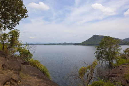 sri lankan sorabora lake with wooded hills and rock formations at a popular picnic site under a blue sky with white cloud
