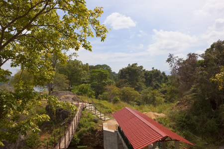 a popular sri lankan picnic site at sorabora lake in the central district with a footbridge and tropical forest under a blue cloudy sky Reklamní fotografie
