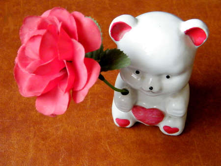 White ceramic teddy bear with a red rose on a brown background photo