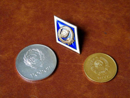 Gold (Uzbekistan) and silver (Russia) medals for excellent high school graduation in the Soviet Union and University badge (Soviet Union) on a brown background photo