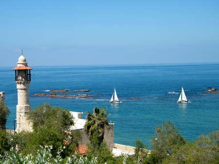 Minaret of Al-Bahr Mosque and White Yacht in blue Mediterranean Sea in old city Jaffa, Israel    photo