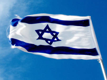 Flag of Israel against blue sky in Tel Aviv, Israel                              photo