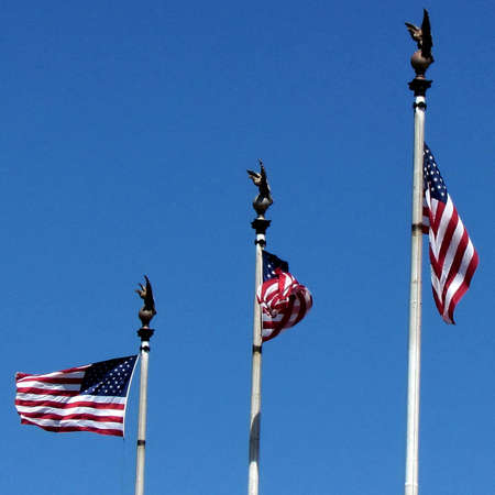Three flags of the United States in front of the building of Union Station in Washington DC, USA