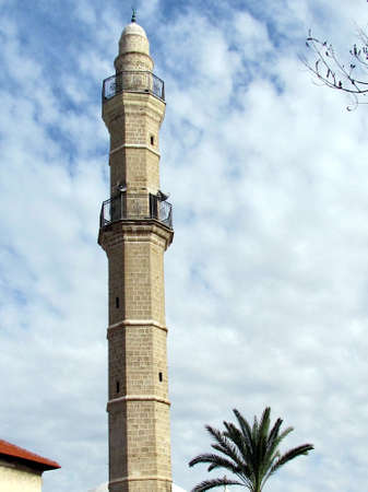 The minaret of Great Mosque Muhamidiya Mosque on background of cloudy sky in old city Jaffa, Israel