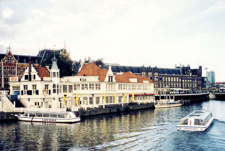 gabled house: The excursion vessels on canal in Amsterdam, Netherlands Stock Photo