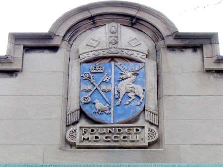 pediment: Foundation year and logo on the pediment of Trinity College at University of Toronto in Toronto Ontario, Canada