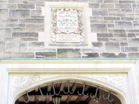 pediment: The founding year and emblem on the pediment of Trinity College at University of Toronto in Toronto Ontario, Canada