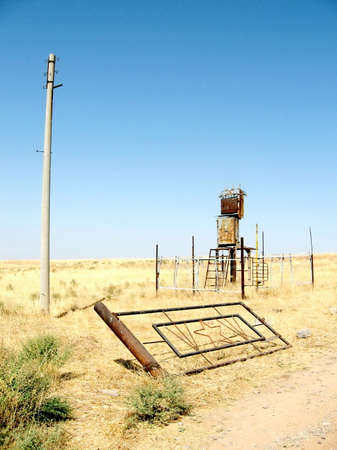 The ruins of the power line and the gate in the steppe near Mayskiy, Uzbekistan Imagens