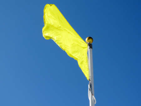 Yellow flag on flagpole flying in the wind in High Park of  Toronto, Canada, February 16, 2017 Stock Photo - 72427667